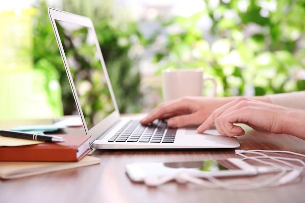 Mani femminili che lavorano con un computer portatile all'aperto su sfondo sfocato di piante verdi