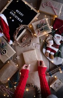 Mani femminili che avvolgono i regali di natale in carta del mestiere