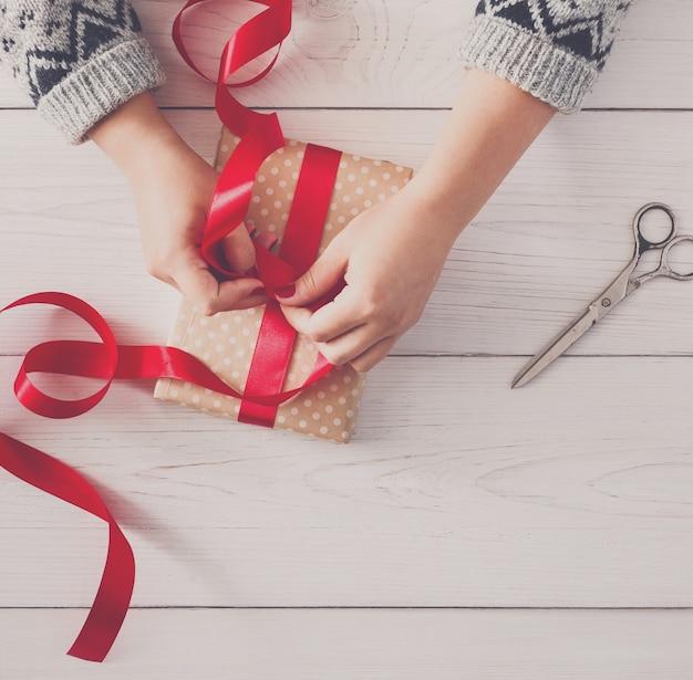 Mani femminili che avvolgono il regalo fatto a mano di natale in carta