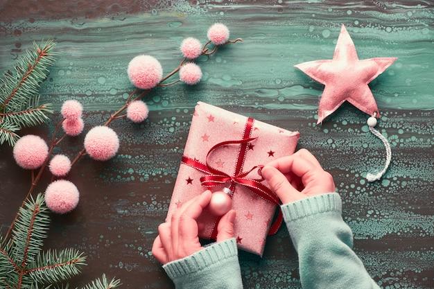 Mani femminili che avvolgono regalo di natale, decorazioni invernali e ramoscelli di abete. natale piatto disteso in blu, nero e rosa