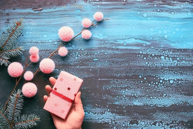 Mani femminili che avvolgono regalo di natale, decorazioni invernali e ramoscelli di abete. natale piatto disteso con copia-spazio in blu, nero e rosa sulla parete del liquido liquido acrilico astratto.