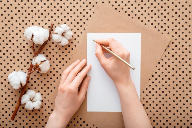 Le mani femminili scrivono una lettera sul tavolo con fiori di cotone che sbocciano. la donna fa la lista dei desideri o fa la lista piatta. la ragazza scrive la cartolina d'auguri del segno.
