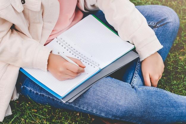 Le mani femminili scrivono in un taccuino.