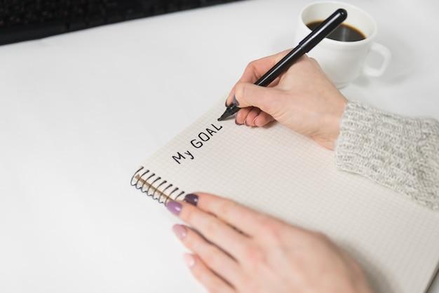 Mani femminili che scrivono i miei obiettivi in un taccuino. tazza di caffè sul tavolo. avvicinamento