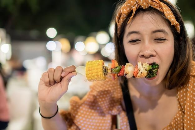 Femmina felice e deliziosa di mangiare carne di maiale a cubetti magra barbecue con verdure di mais
