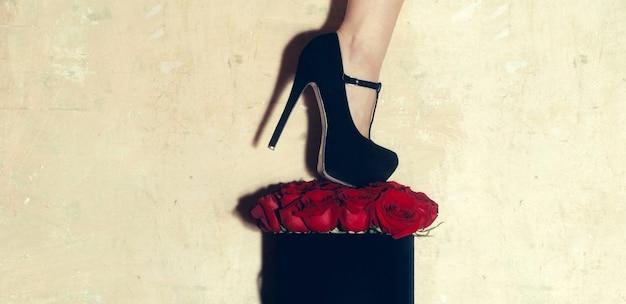Tacchi alti femminili sul mazzo di rose rosse di fiori naturali freschi nella casella attuale nera
