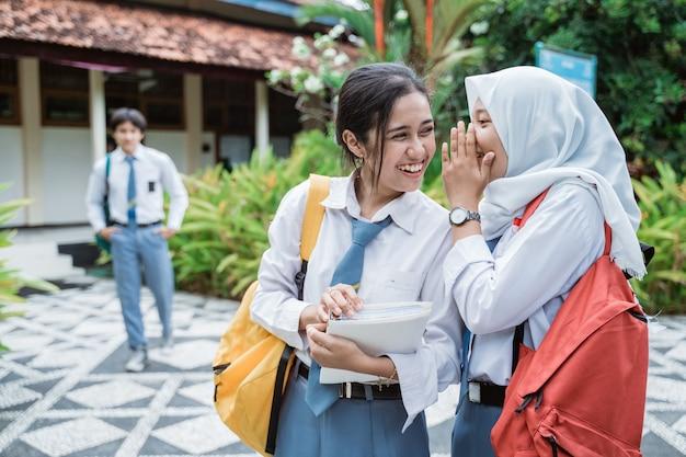 Studentessa di scuola superiore con uno studente di scuola superiore maschio in piedi in lontananza