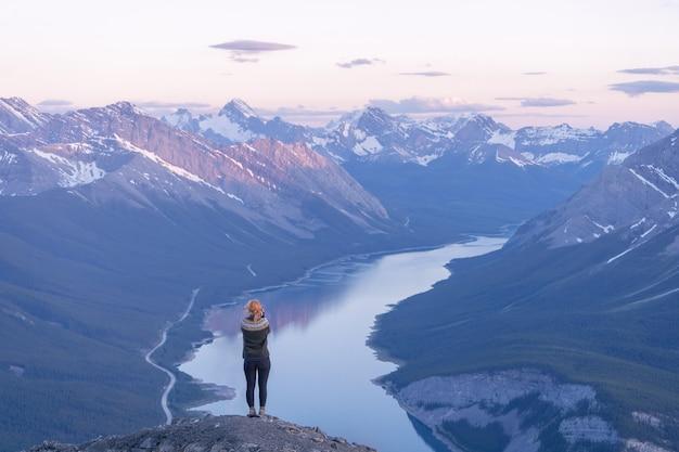 Escursionista femmina godendo della vista sulla valle alpina durante il tramonto rimwall summitcanada
