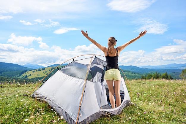 Viandante femminile in una tenda in montagna