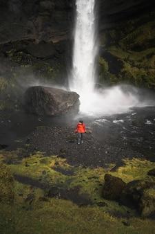 Escursionista femmina con vista sulla cascata kvernufoss nel sud dell'islanda
