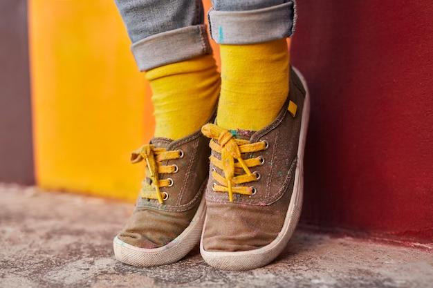 Hipster femminile in scarpe di stoffa e calzini gialli luminosi