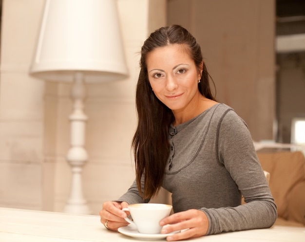 Femmina che tiene una tazza di caffè