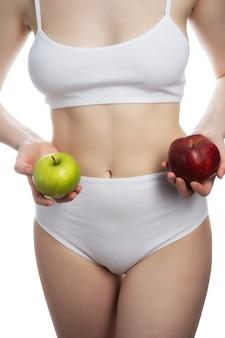 Una femmina in possesso di un mele rosse e verdi in diverse braccia isolate sul muro bianco. concetto di cure odontoiatriche