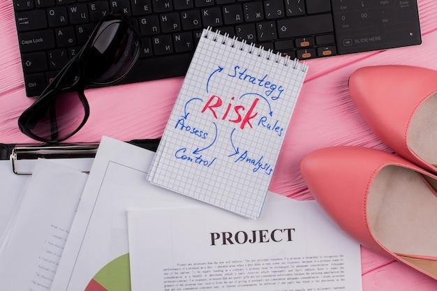 Scrivania da ufficio femminile con occhiali e scarpe per il blocco note