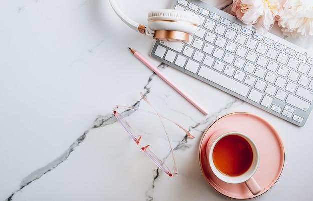 Area di lavoro femminile dell'ufficio domestico con una tazza di tè e fiori di peonia su sfondo di marmo bianco vista dall'alto f...