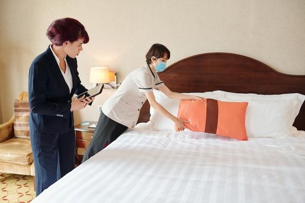 Direttore d'albergo femminile che guarda la cameriera in maschera medica che fa il letto e aggiusta i cuscini nel suo primo giorno di lavoro