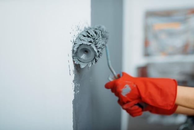 Mano di imbianchino femminile con rullo di vernice contro il muro. riparazione domestica, donna che ride facendo ristrutturazione appartamento, ristrutturazione camera