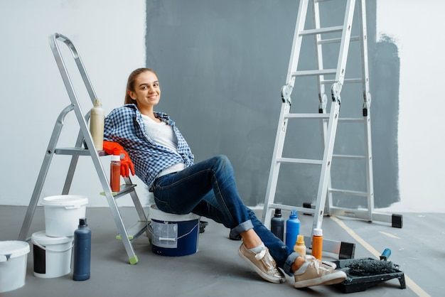 Imbianchino femminile che si rilassa su un ritardatario. riparazione domestica, donna felice che fa rinnovamento dell'appartamento, rinnovamento della decorazione della stanza