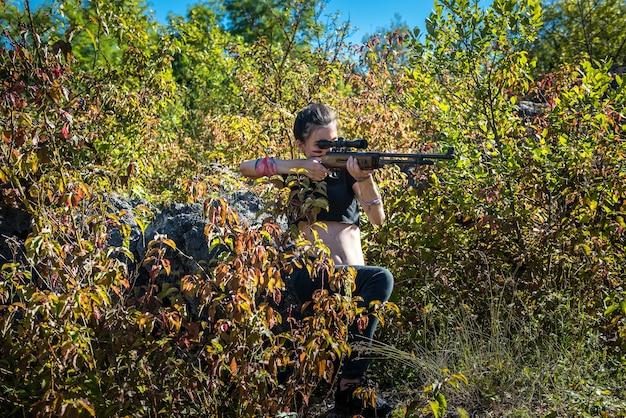 Cacciatore femminile in cima usando un'arma o un fucile in natura, all'aperto