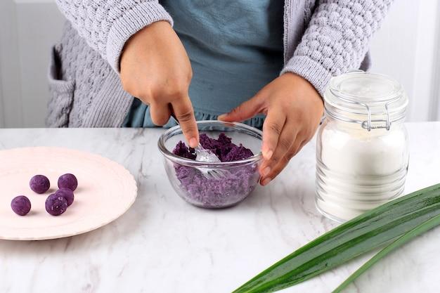 Processo di patate dolci viola al vapore schiacciato a mano indonesiano femminile che produce biji salak ubi ungu