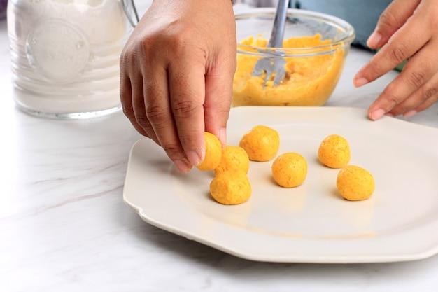 Femmina indonesiana put biji salak kabocha, torta di riso gialla di patate dolci o zucca, processo di cottura in cucina fare takjil per buka puasa ramadan breakfasting