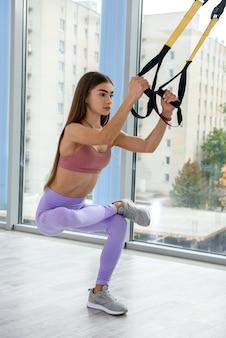 Istruttore femminile che mostra la mano di esercizio facendo allenamento urbano per braccia e petto con cinghie fitness trx. concetto di stile di vita sano