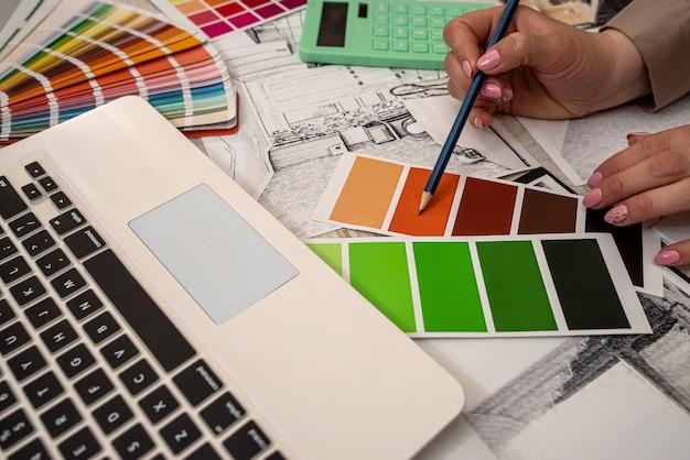 La designer d'interni donna sceglie il colore dalla tavolozza, lavorando con lo schizzo della casa in ufficio
