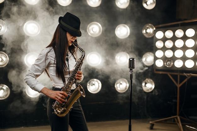 Il musicista jazz femminile in cappello suona il sassofono sul palco con faretti. artista jazz che suona sulla scena