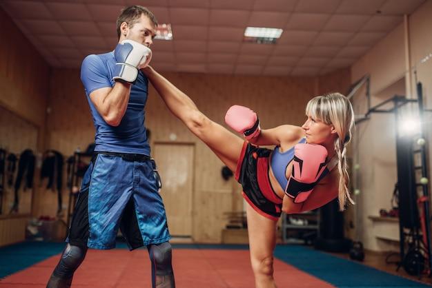 Kickboxer femminile praticando calci con personal trainer maschile, allenamento in palestra. il pugile colpisce in allenamento, pratica di kickboxing