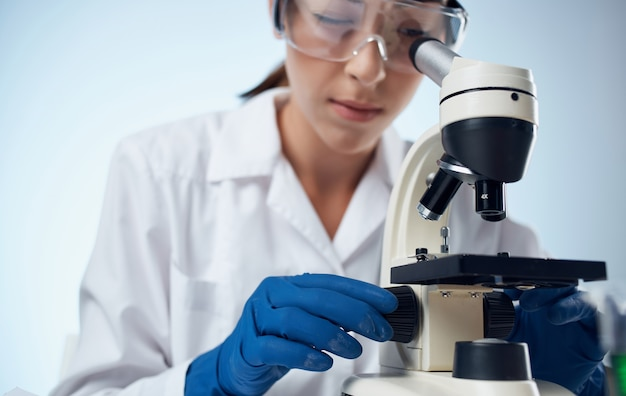 Assistente di laboratorio femminile esamina i batteri attraverso un microscopio e occhiali sulla vaccinazione dell'elemento chimico del viso.