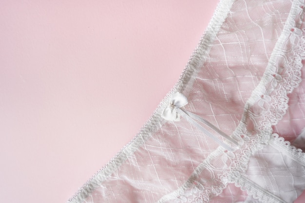 Mutandine femminili del pizzo su fondo rosa con lo spazio della copia. panno di moda, lingerie