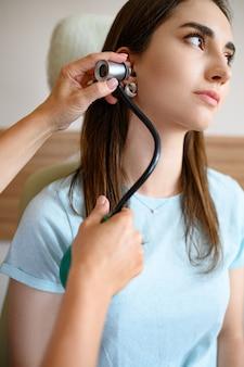 Laringologo femmina con otoscopio e paziente in sedia. esame dell'orecchio in clinica, diagnostica professionale, medico ent. medico specialista e donna in ospedale,