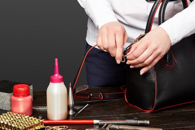 Leathercrafter femminile che attacca la cinghia alla borsa sul posto di lavoro