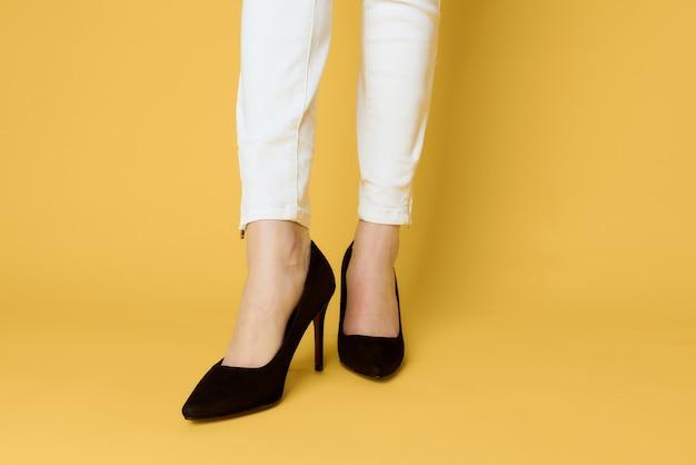 Piedini femminili scarpe nere moda look attraente jeans bianchi gialli