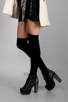 Piedini femminili in calze e stivali neri