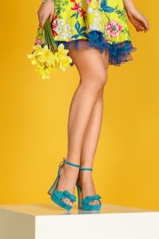 Piedini femminili in scarpe blu su sfondo giallo. umore primaverile