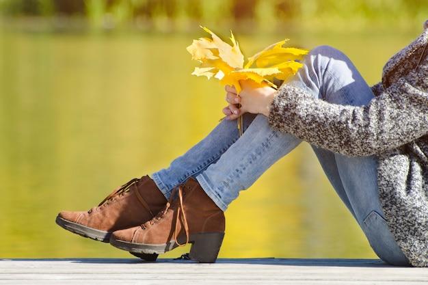 Gambe femminili in scarpe marroni sullo sfondo di un fiume. giorno d'autunno
