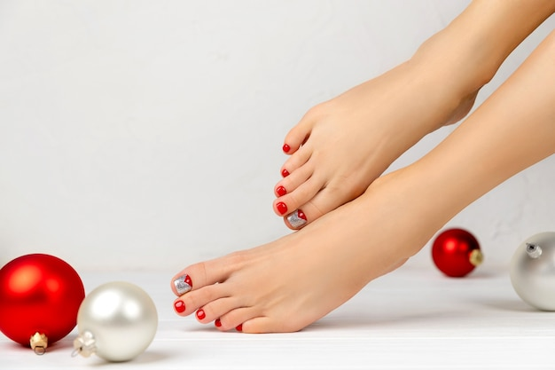 Piedini femminili e ornamenti natalizi. concetto di salone di bellezza manicure pedicure.