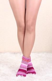 Piedini femminili in calzini colorati sulla superficie del tappeto bianco