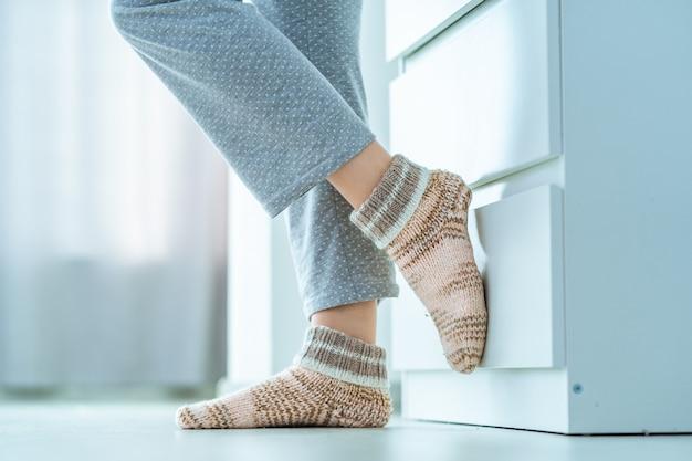 Gambe femminili in calzini invernali lavorati a maglia morbidi e confortevoli a casa