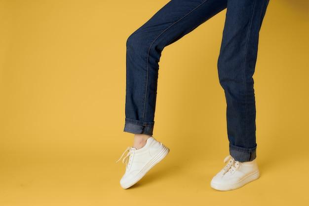 Gambe femminili ritagliate vista graduale scarpe bianche stile moderno sfondo giallo