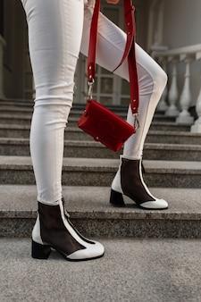Gambe femminili in scarpe alla moda in jeans alla moda con una borsa di cuoio rossa su una scala di pietra