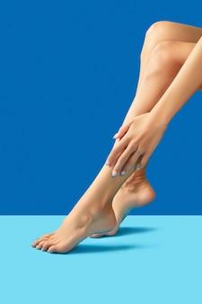 Gambe e mani femminili con design delle unghie blu alla moda