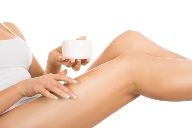 Gambe e mani femminili con un barattolo di crema. donna che applica idratante sulle sue gambe perfette, isolate su fondo bianco.