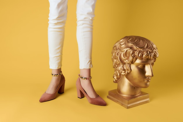 Lusso delle gambe femminili che posano il lusso del busto dorato