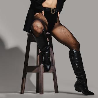 Piedini femminili in mutandine, collant e stivali da equitazione in pelle che si siede sulla sedia in studio
