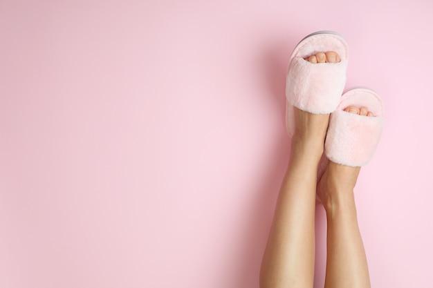 Gambe femminili in pantofole rosa su rosa