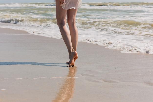 Piedini femminili in riva al mare. chiuda in su del corpo della donna giù sul mare e sulla sabbia