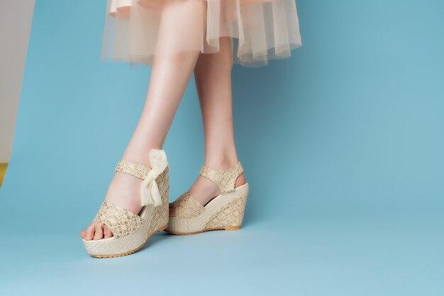 Le gambe femminili in scarpe vestono la moda tagliata del fondo blu del primo piano di vista