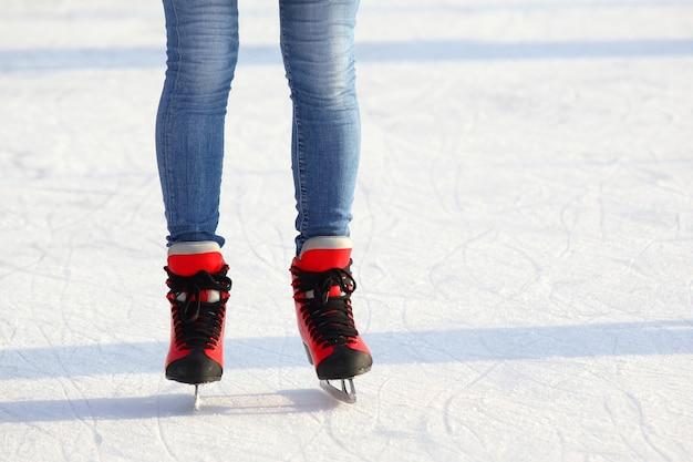 Piedini femminili in pattini su una pista di pattinaggio sul ghiaccio